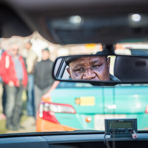 A Photograph Of The Reflection Of A Taxi Driver Through The Rearview Mirror. We See His Eyes And Nose As He Is Driving And Looking Out The Front Window. The Car In Front Is An Orange And Green Taxi..