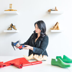 A Photograph Showing A Person With Long Black Hair And A Black Jacket Holding Up A High Heeled Shoe As They Are Looking At It. On The White Table In Front Of Them Are What Looks Like Shoes Being Made. Behind The Person Is A White Wall With Shelves Of Shoes.