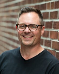 A headshot of Henry, with a black shirt and glasses on. He is smiling directly at the camera and standing in front of a brick wall.