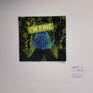 A Picture Of Hanan's Artwork On A Gallery Wall. It Depicts A Person With Their Hands Over Their Face, With Many Skulls In The Background. The Colours Have Been Altered To Be Green And Blue. The Text Overlay Reads,
