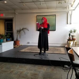 A Photo Of Hanan Standing On A Platform, Reading A Book Into A Microphone. She Is Wearing A Black Dress With A Red Headdress.