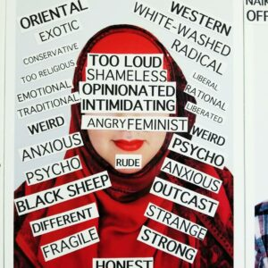 A Photo Of One Of Hanan's Art Pieces. It Shows A Picture Of A Person With Red Lipstick And A Red Headdress. There Are Many Cut Outs Of Text Covering The Picture, Including The Person's Eyes And Nose. Some Examples Of The Words Are: Too Loud, Shameless, Opinionated, Intimidating, Angry Feminist, Rude, Western, Radical, Oriental, Exotic, Psycho, Anxious, Honest.