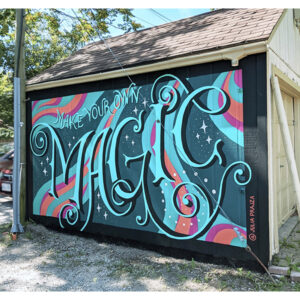 A Photo Of A Mural On The Side Of A Garage That Reads 'Make Your Own Magic' In Bright Blue Hand-lettering. It Is Set On A Blue, Pink, And Orange Swirling Background.