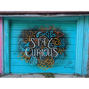 """A Photo Of A Garage Door Painted Bright Blue. In The Center It Reads, """"Stay Curious"""" In White Hand-lettering. Decorative Swirls And Motifs In Blue And Gold Spread Out From The Words."""