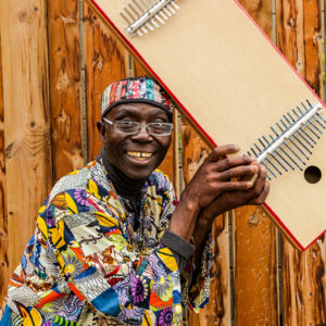 A headshot of Njacko Backo. He has dark skin and is smiling at the camera. He wears rectangular frame glasses, wears bright patterned clothing and is holding up a kalimba.