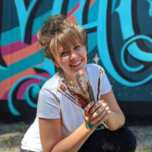 A headshot of Julia Prajza. She has blond hair tied up in a messy bun, light skin, a white shirt, and paint splattered pants. She's holding a handful of paint brushes that are also splattered with old paint. She's smiling and crouching in front of one of her murals.