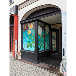 """A Photo Of Storefront Windows. They Are Painted With Yellow And White Flowers On A Bright Blue Background. In Cursive Hand-lettering It Says, """"Stay Wild & Free""""."""