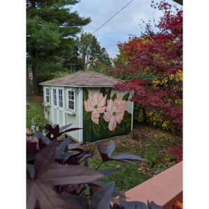 An Outdoor Shot Of A Garden Shed. It Has A Mural On The Side Closest To The Camera Featuring Pale Pink Flowers On A Leafy Forest Green Background.