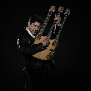 """A Photo Of Yannis Kapoulas Holding A Triple Neck Guitar. He Is Wearing A Black Leather Jacket. The Guitar Is Made Of A Light Wood With His Name, """"Yiannis K"""", Scrawled On The Front."""