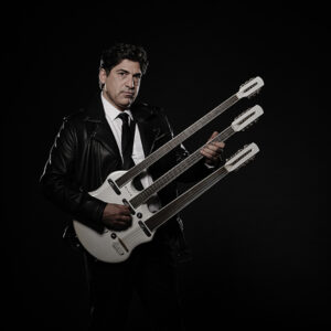 A Photo Of Yiannis Kapoulas With A White Triple-neck Guitar. He Is Wearing A Black Leather Jacket And Looking At The Camera.