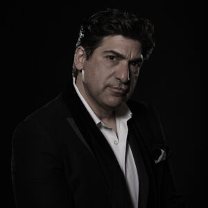 A headshot of Yiannis Kapoulas. He is wearing a black blazer with a white pocket square and white shirt underneath. The portrait is dramatically lit and set on a black background. He has short black hair, light skin, and a neutral expression.