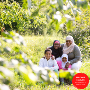 An Outdoor Shot Of A Family. There Are Three Women Wearing Hijab And A Boy With Short Curly Hair Crouched In A Grassy Field. They Are Smiling At The Camera.
