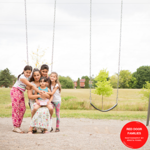 A Shot Of A Woman And Her Four Children Sitting On A Swing Set. The Woman Sits On The Swing With The Smallest Child In Her Lap. A Child Stands On Either Side Of Her And One Behind Her.