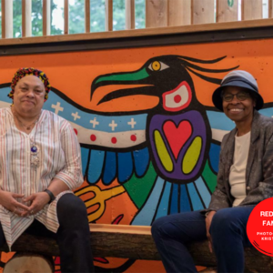 A photo of Carol and Bernnitta sitting in front of a bright mural by Indigenous artists Philip Cote. The mural is an Indigenous-style bird with wings spread wide. The person on the left has medium-dark skin and wears a striped top. The person on the right has dark skin, a blue bucket hat and a gray blazer. They are smiling.