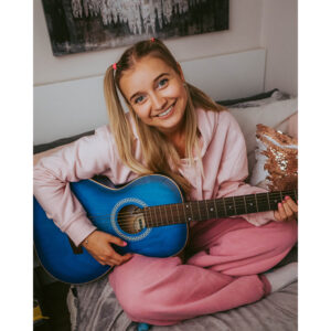 A Photo Of Millie Bee In Pink Sweatpants And Hoodie. She's Smiling And Playing A Blue Guitar.
