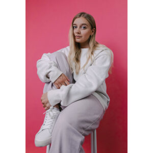 A Photo Of Millie Bee In A White Outfit Perched On A Stool. She's Sitting In Front Of A Bright Pink Backdrop. She's Wearing Pale Pink Eyeshadow And Looking At The Camera.