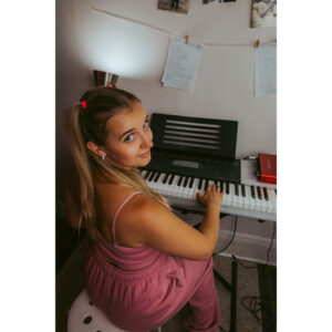 An Over-the-shoulder Shot Of Millie Bee. She's Sitting At An Electric Keyboard Wearing Pink Sweatpants And A Pink Top.