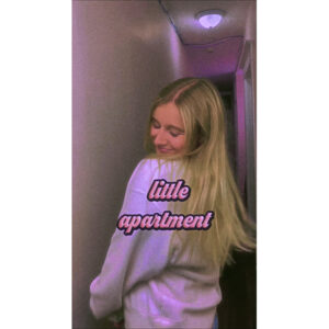 """A Photo Of Millie Bee In A Narrow White Hallway. In The Centre Of The Photo Reads, """"little Apartment"""" In A Pink Cursive Font."""