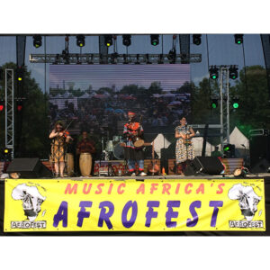 """A Photo Of The Band, Kalimbas At Work, On Stage. Across The Front Of The Stage A Banner Reads, """"Music Africa's Afrofest"""". Njacko Backo Is Centre Stage."""