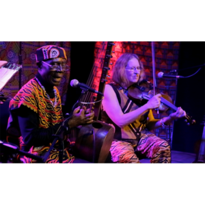 A Photo Of Njacko Backo Performing Next To A Violin Player. Njacko Backo Plays A Ngoni While Singing Into A Microphone.