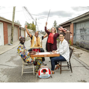 A Photo Of The Band, Kalimbas At Work, In An Alleyway. In The Foreground A Colourfully-dressed Njacko Backo Sits With A Person In A White Top Supporting A Kalimba Between Them. Behind The Kalimba Are Two People. One Sits At A Conga Drum And The Other Stands, Holding A Violin Up. Everyone Is Smiling.