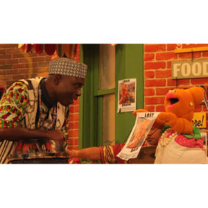 """A Photo Of Njacko Backo With A Hand Puppet. Njacko Backo Is On The Left Wearing African Style Clothing, He Is Speaking With An Orange Hand Puppet Wearing An Apron And Pearl Necklace. The Puppet Holds Up A Poster That Reads, """"LOST"""" Across The Top."""