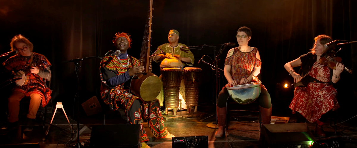 A banner image featuring the band, Kalimbas at Work. The band features five people playing on a warmly lit stage. They each play a different acoustic instrument, Njacko Backo sits in the foreground singing into a microphone.