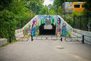 An exterior shot of a mural on the face of a tunnel. A walking path leads through the tunnel. The mural features four colourfully rendered people gardening together.