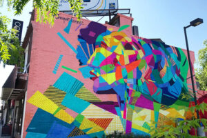 A picture of a mural that covers the entire side of a two-story building. Colourful abstract shapes form the impression of a woman's profile on a light pink background.
