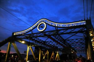"""A photo of an iron bridge set against a dark purple cloudy sky. The bridge structure is under-lit. Across the top reads, """"This river I step in is not the river I stand in."""" The words arch over a lit-up clock."""