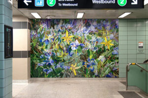 An interior shot of Chester subway Station. On a teal tile wall is a vibrant mural featuring yellow and blue flowers on a green grassy background.