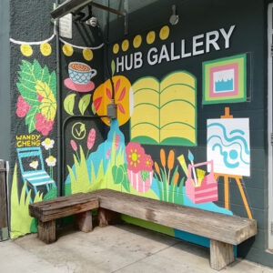 Photograph Of A Colour Mural With Hub Gallery On The Wall And A Wooden Bench In The Front.