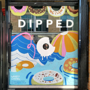 Photograph Of A Window Mural For Dipped Donuts, Depicting Donuts As Floaties.