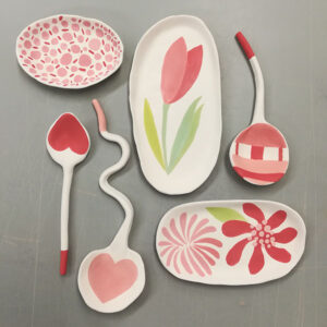 Photograph Of A Pink Assortment Of Bisqued Ceramics, Including Three Spoons And Three Dishes.