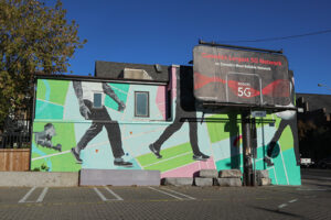A picture of a mural. The mural takes up the full side of a two-story building. It features three figures in grayscale walking on a bright green and blue background.