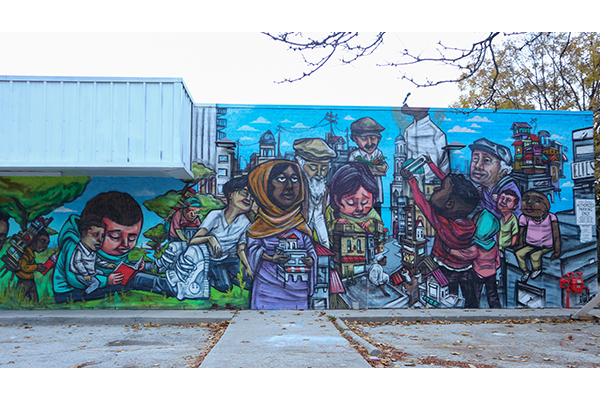 A picture of a mural on the side of a building. The mural is of many people of diverse skin colour and race in amongst recognizable East End landmarks.
