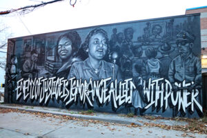 """A picture of a grayscale mural, in bold letters it reads, """"the enemy of justice is ignorance allied with power"""". At the centre of the mural is two women, one speaks into a microphone."""