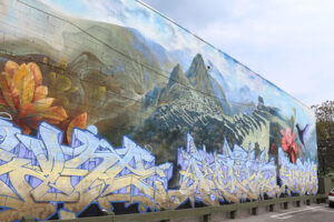 A picture of a massive mural on the side of a building. Across the bottom in blue and yellow are three graffiti style words. Behind them rises a realistically rendered Machu Pichu.
