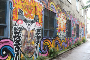 A picture of a mural along a long wall. The mural is chaotic and vibrant, featuring bright oranges, pinks and purples. There are several faces painted between windows, along the bottom are swirling waves with bold black outlines.