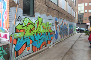 A photo of an alley way. Vibrant graffiti-style words cover the wall. Nearest to the camera is bright green and blue street art.
