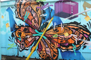 A picture of a mural featuring a bright orange butterfly on a light blue background. The line work is expressive and bold.