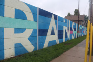 """A picture of a wall painted in blocky blue tiles. In large white block letters reads, """"Transitions""""."""