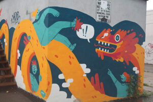 A picture of a mural featuring an orange and yellow Eastern dragon. One person, painted in blue, sits on top of the dragon's back, another person points towards him, seemingly shocked at what they're witnessing. A third figure peers through the loops of the dragon's body.