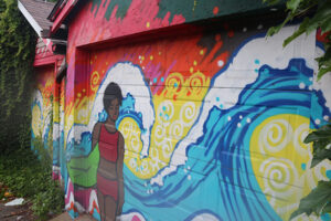 A picture of a mural painted on a garage. The mural is of a person with dark skin in a red bikini. Bright blue waves crash behind her on a vibrant yellow and orange background.