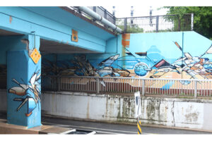 A picture of an underpass painted with a bright blue mural. Beige geometric shapes with bold black lines cut through the blue.