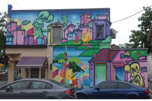 A picture of a pastel-coloured mural on the side of a building. At the front of the building is a storefront with a purple awning. The mural features stylized bunnies throughout a pink-tinted urban scene.