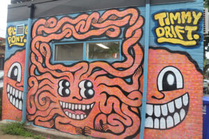 A picture of a mural featuring an orange creature with many noodle-like arms, four eyes and a grinning mouth.