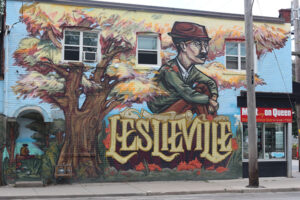 """A picture of a mural on the side of a building. The mural features a tree with bright orange, red, and yellow leaves. Across the bottom in decorative text reads, """"Leslieville"""". A man sits on the word, he is earing a green jacket, has a pencil tucked behind his ear and sits hugging his knees."""