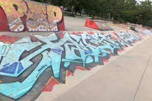 A picture of a skatepark incline. Across the cement incline bright blue graffiti is painted on a red paint-splatter style background.