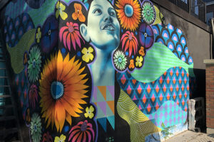 A picture of a colourful mural. At the centre is a portrait painted in blues and teals. Bright flowers surround them with geometric patterns flowing outward in blue and pink and orange.